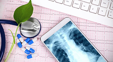 Picture of keyboard, phone with xray, stethoscope and medicine.