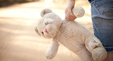 Image of a girl holding a teddy bear.